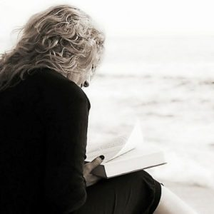 A woman sits in the sand at the beach reading a book