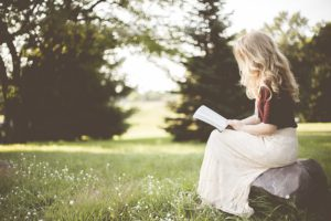 A Woman with blond hair wearing a flowy white skirt sits off to the right reading a book with a nature scene of grass and trees behind her