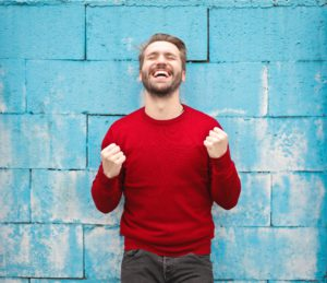 A man wearing a red sweater stands in front of a blue brick wall smiling with clenched fists, feeling successful