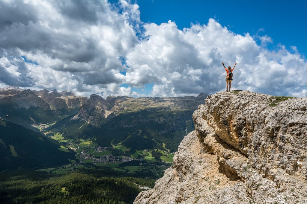 Woman standing on top of a mountain overlooking a gorgeous mountain view with fluffy clouds