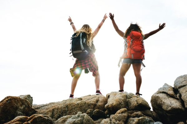Two women wearing backpacks stand with arms above their heads successfully climbed a mountain