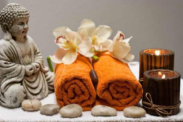 A budha figurine overlooks two orange towels rolled with flowers draped on top