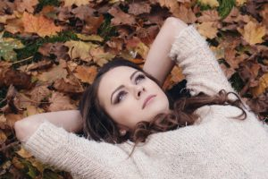 A woman looking deep in thought lies on the ground over top of orange and brown fallen leaves