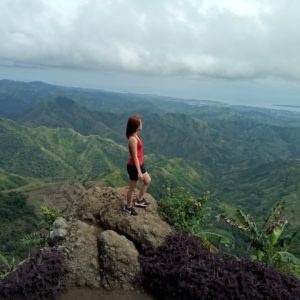 A woman wearing a bright red shirt stands on top of a mountain that she's climbed, looking out at a gorgeous landscape.