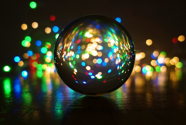 A clear crystal ball is in the foreground with shiny lights in the background