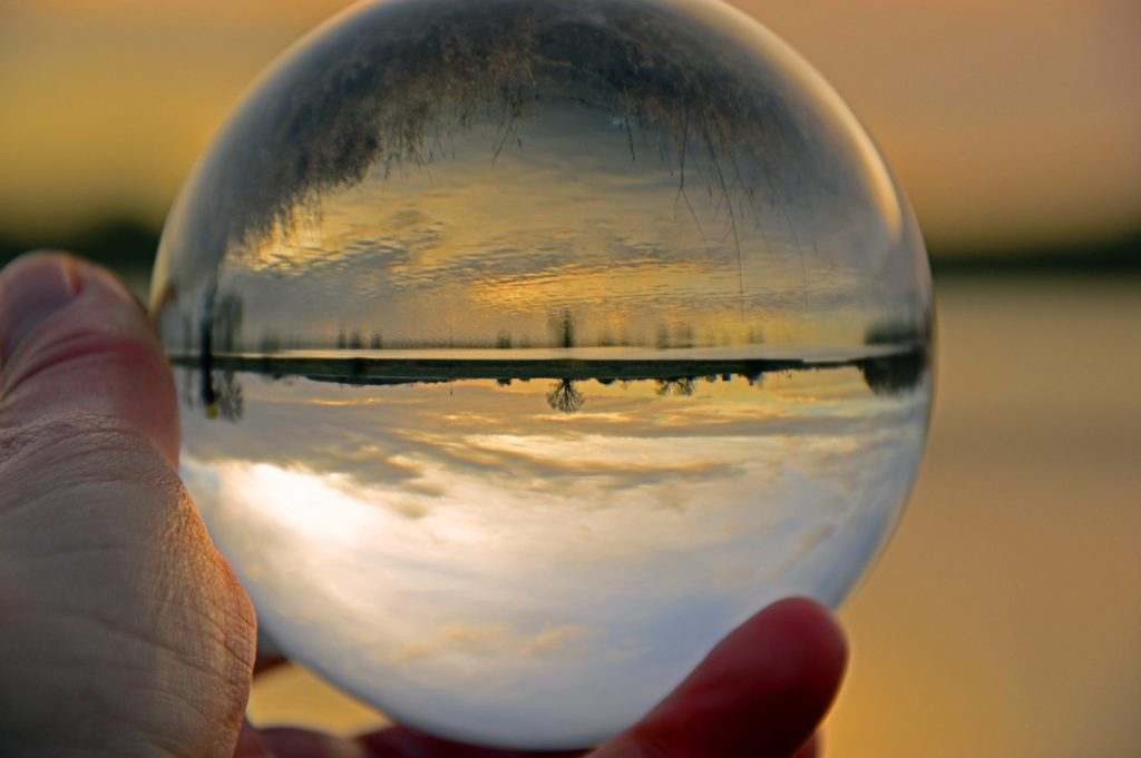 A hand holds a clear sphere with a snowy landscape reflecting in it.