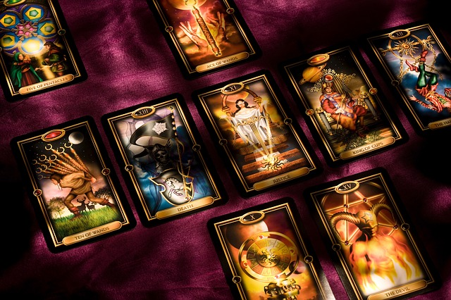 A gorgeous deck of colourful tarot cards are spread on a purple cloth