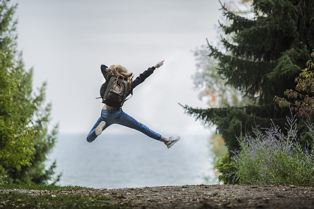 A young lady with a backpack on jumps up with excitement on a path surrounded by trees.