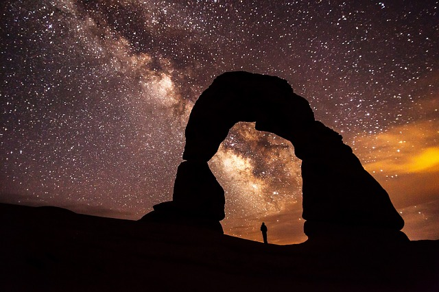 A man stands under a rock giant under a purple milky-way star-filled sky.