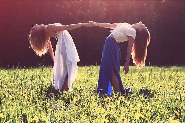 Two women link arms doing back bends in a field of wild flowers.