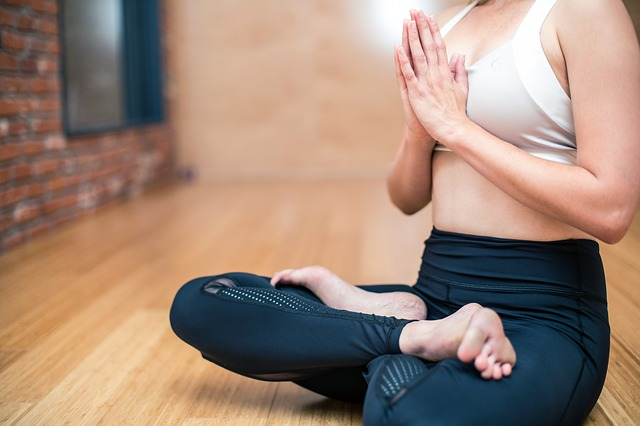 A woman sits cross-legged holding prayer hands to her chest wearing yoga clothes.
