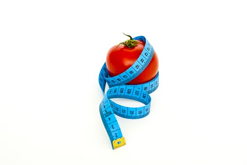 A red apple surrounded by a blue measuring tape. Eating healthy to bring your desired outcome.